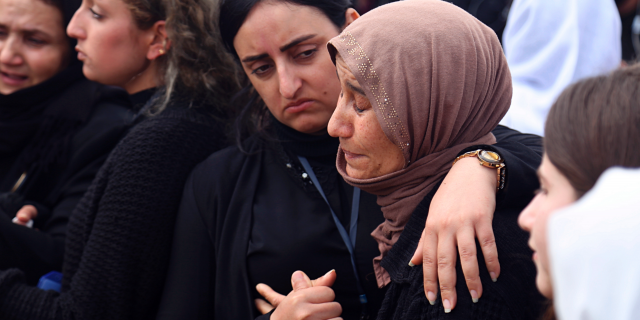 In this March 15, 2019 file photo, Iraqi Yazidi women mourn during the exhumation process of a mass grave in Iraq's northwestern region of Sinjar.