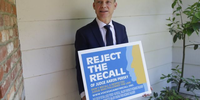 "Aaron Persky holds a ""Reject the Recall"" placard in Los Altos Hills, Calif., May 15, 2018. (Associated Press)"