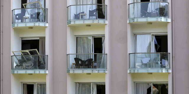 A worker on a balcony, below right, cleans up the debris after an explosion at an army's munitions depot near the coastal city of Kyrenia in the Turkish occupied area at northern Cyprus, Thursday, Sept. 12, 2019.