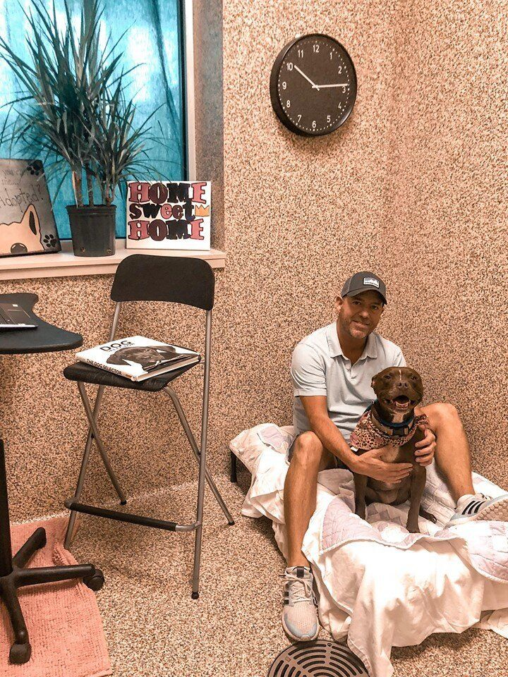 Scott Poore poses with Queen, a 3-year-old terrier mix, in their room at the Great Plains SPCA in Kansas City.