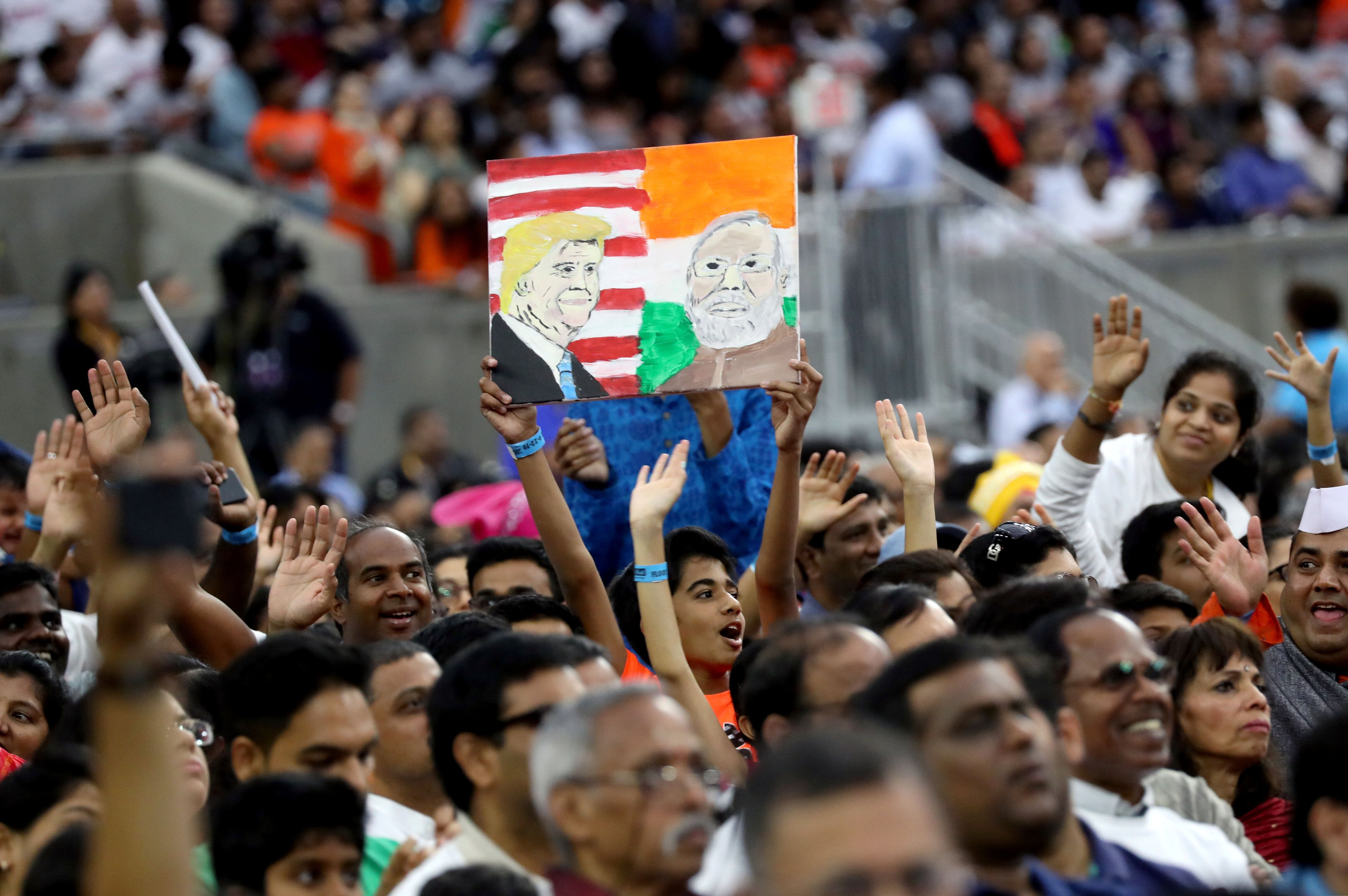 """A boy holds a placard depicting President Donald Trump and India's Prime Minister Narendra Modi during the """"Howdy Modi"""" event"""