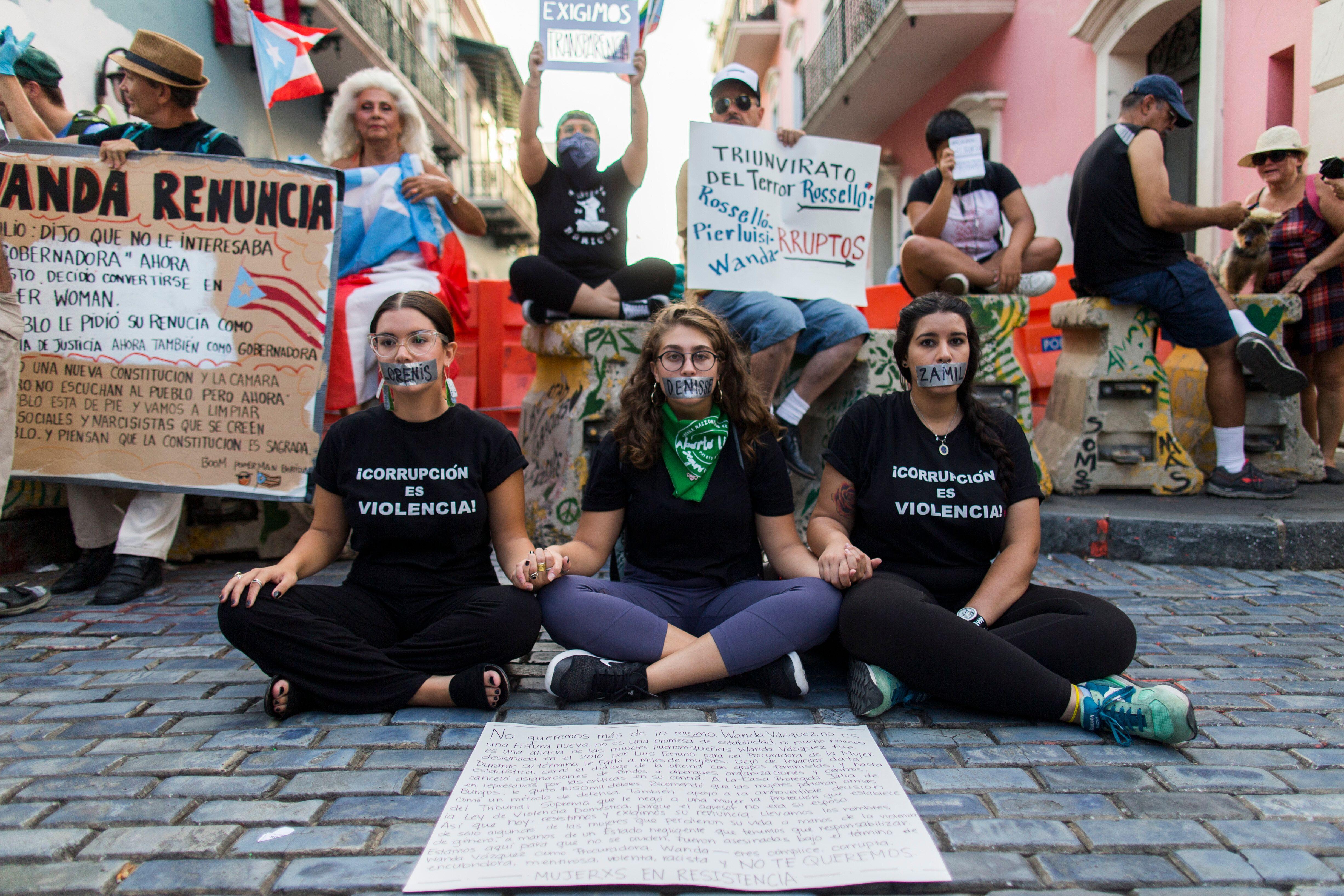 Tres mujeres protestan con otros manifestantes afuera de La Fortaleza, la mansión del gobernador, en San Juan el 9 de