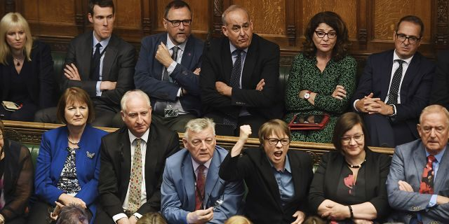 In this handout photo provided by the House of Commons, opposition MP's look on as Britain's General Attorney Geoffrey Cox speaks in Parliament in London, Wednesday, Sept. 25, 2019.