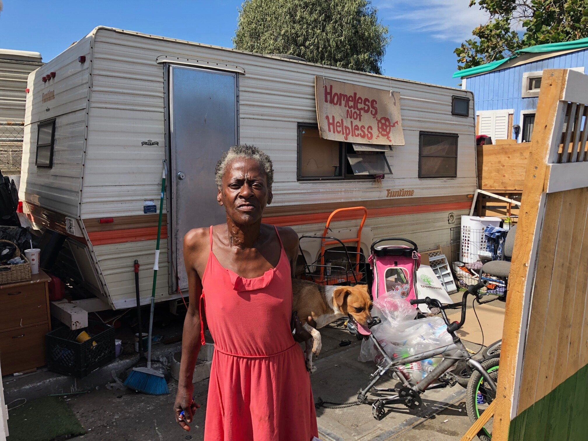 """Claudette Smith stands in front of her mobile home in an Oakland homeless encampment, with a sign that reads: """"Homeless not h"""