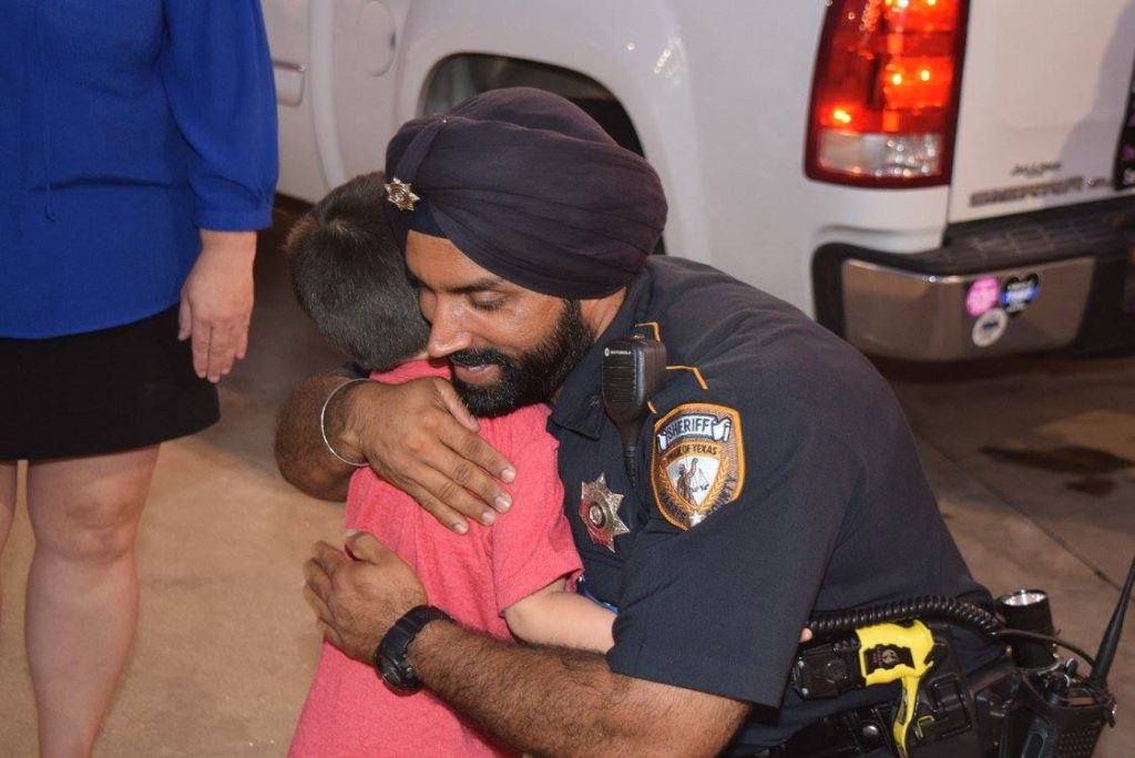 Deputy Sandeep Dhaliwal talks with a young boy at a memorial at the scene of the August 2015 rutal murder of fellow Deputy Darren Goforth. (Breitbart Texas Photo: Lana Shadwick)