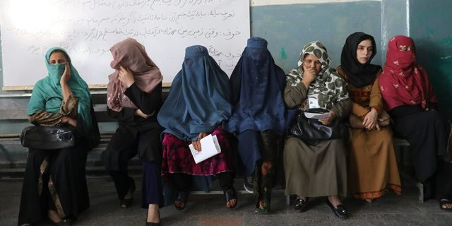 Afghan women wait for the a polling station to open in Kabul, Afghanistan, Saturday, Sept. 28, 2019. Afghans headed to the polls on Saturday to elect a new president amid high security and Taliban threats to disrupt the elections, with the rebels warning citizens to stay home or risk being hurt. (AP Photo/Ebrahim Nooroozi)