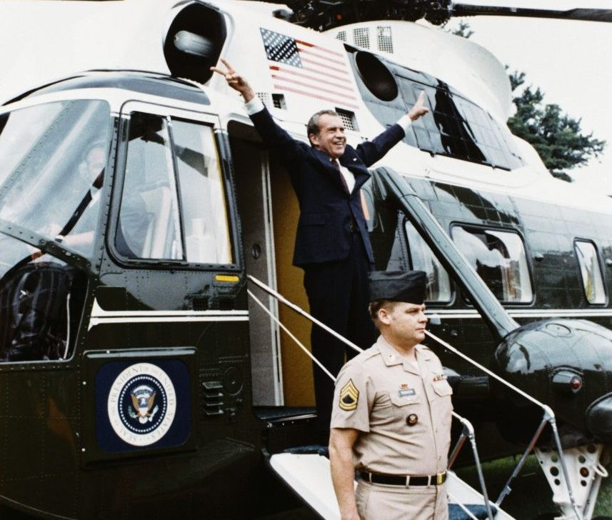"""President Nixon gives his famous """"V"""" sign as he departs the White House for the last time"""