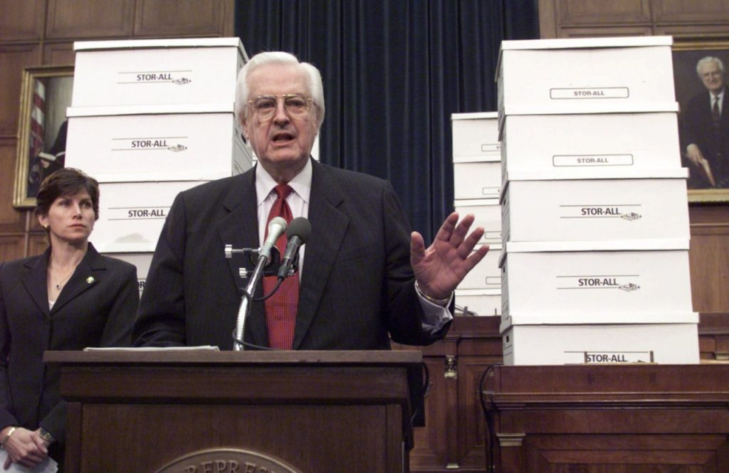 """Surrounded by boxes of evidence against President Clinton, House Judiciary Committee Chairman Rep. Henry Hyde, R-Ill., accompanied by committee member Rep. Mary Bono, R-Calif., gestures during a Capitol Hill news conference to say that the committee has """"made a compelling case"""" for impeachment against the President. Starting Tuesday, the president's attorneys will present a defense before the committee. (AP Photo/Joe Marquette)"""