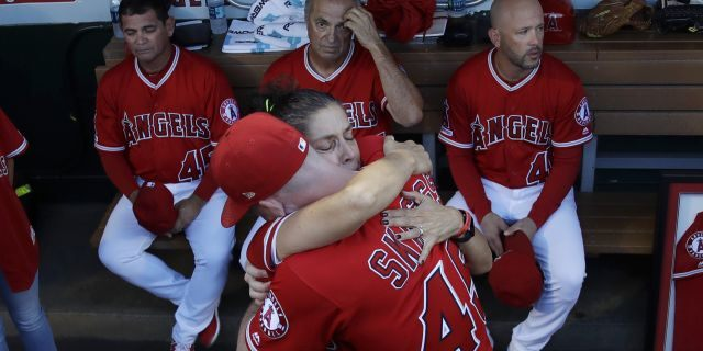 Debbie Hetman, center left, mother of the late pitcher Tyler Skaggs, hugs Angels outfielder Andrew Heaney before the first home game after Skagg's death. (AP Photo/Marcio Jose Sanchez)