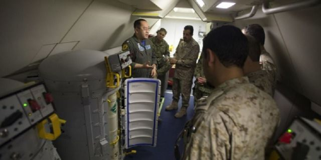 Lt. Fan Yang, left demonstrates the systems on board a P-8A Poseidon aircraft to members of the Royal Saudi Naval Forces on March 1, 2018.