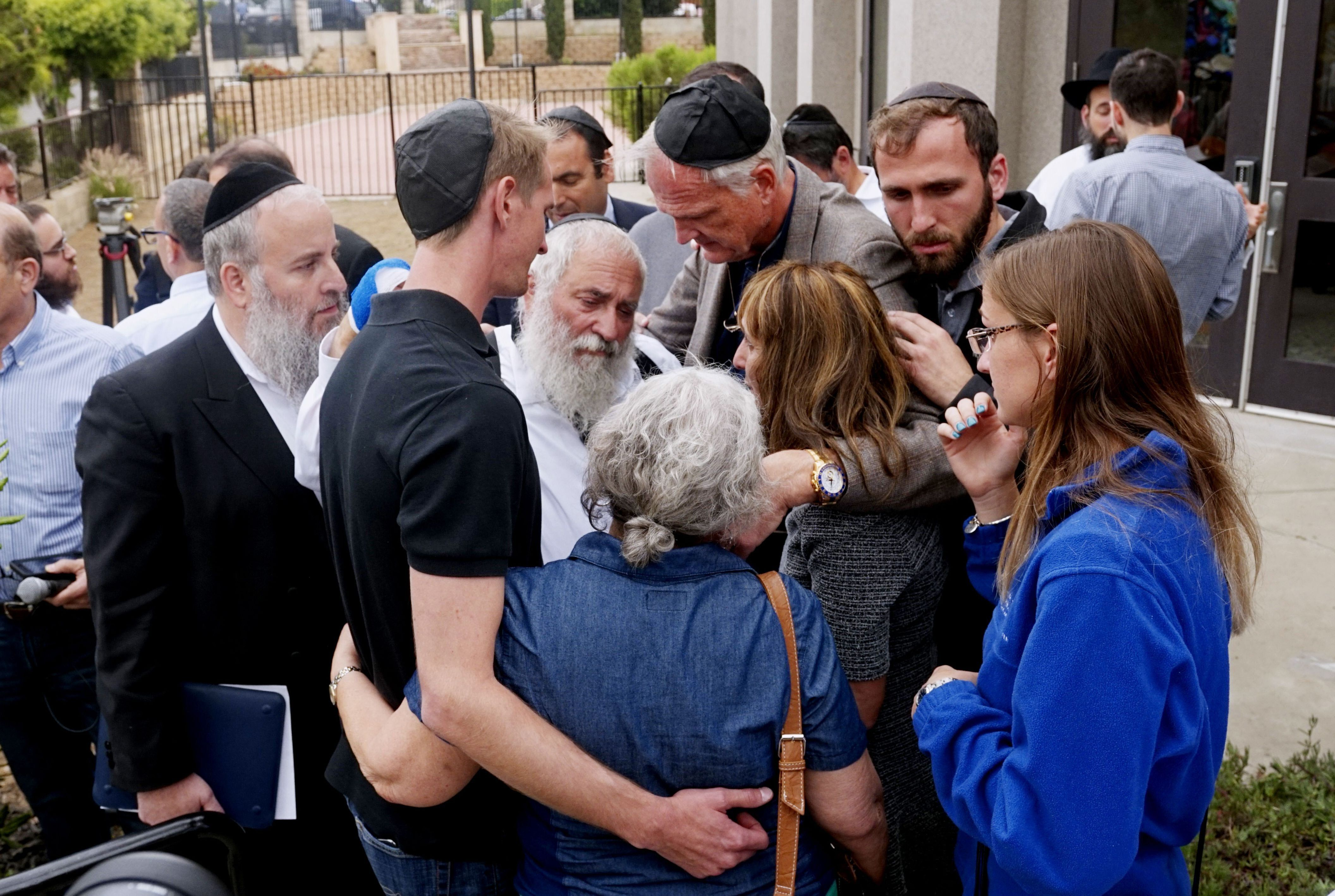 Rabbi Yisroel Goldstein (center) hugs his congregants after a press conference outside the Chabad of Poway Synagogue on April