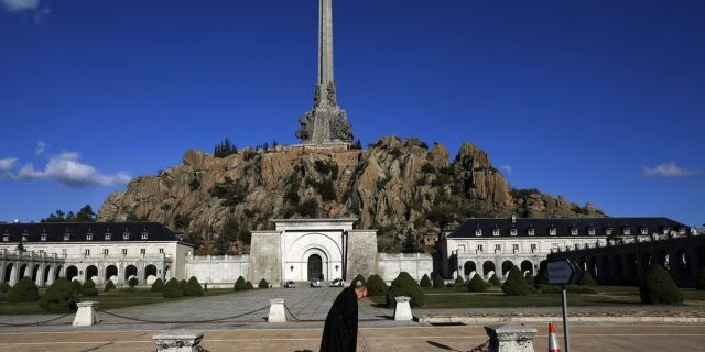 In this photo taken on Sunday, Oct. 13, 2019, A friar walks in front of The Valley of the Fallen mausoleum near El Escorial, outskirts of Madrid. (AP Photo/Manu Fernandez)