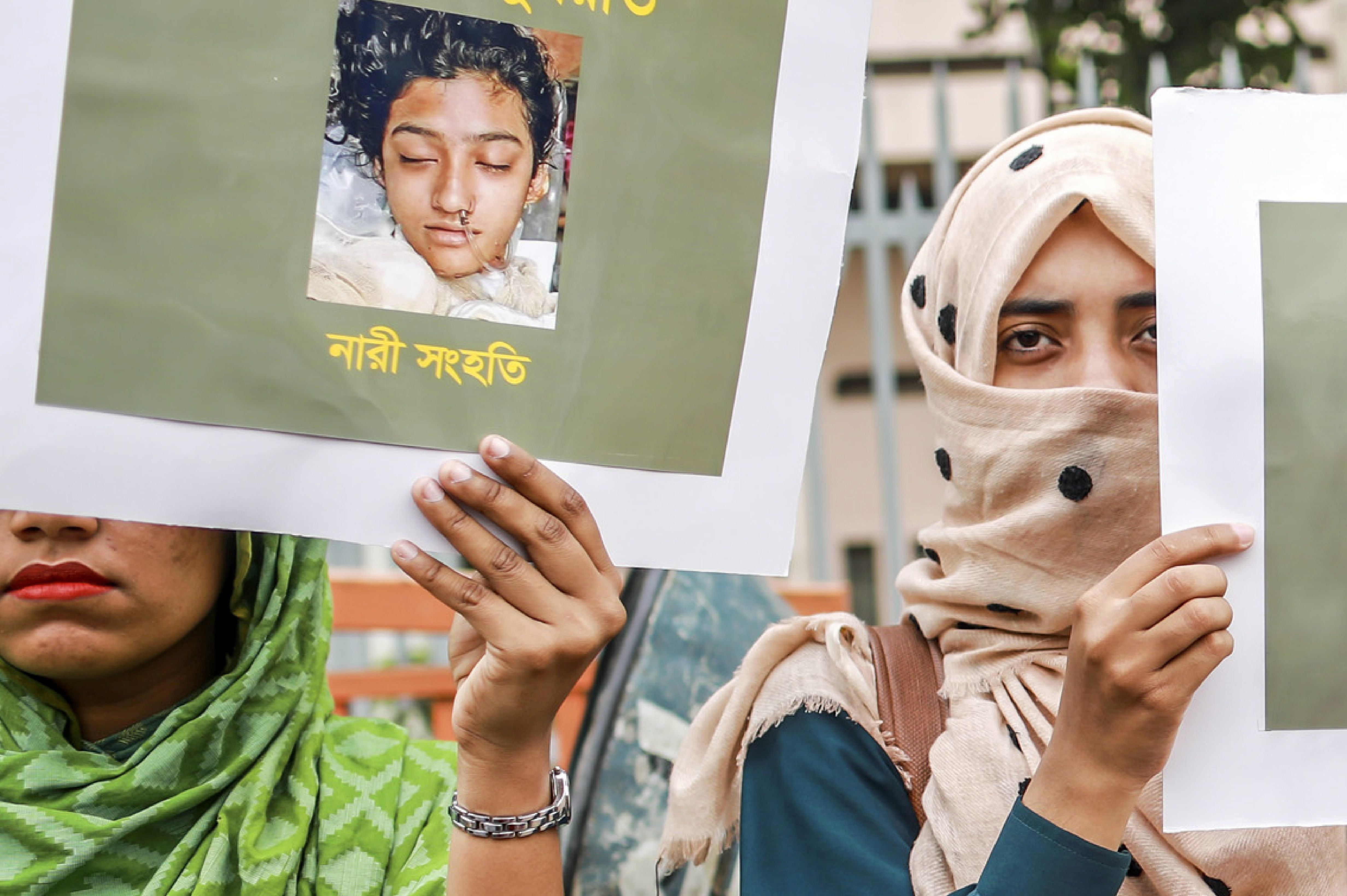 In this photo taken on April 12, 2019 Bangladeshi women hold placards and photographs of schoolgirl Nusrat Jahan Rafi at a pr