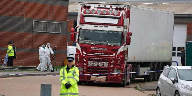 Police forensic officers attend the scene after a truck was found to contain a large number of dead bodies, in Thurrock, South England, Wednesday Oct. 23, 2019. Police in southeastern England said that 39 people were found dead Wednesday inside a truck container believed to have come from Bulgaria.