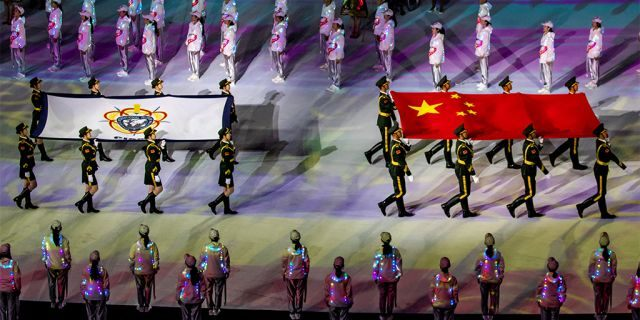 Soldiers from Chinese People's Liberation Army (PLA) parade with a Chinese national flag and a Military World Games flag during the opening ceremony of the 7th CISM Military World Games in China, this month. The Chinese military's orienteering team was disqualified. (Reuters)