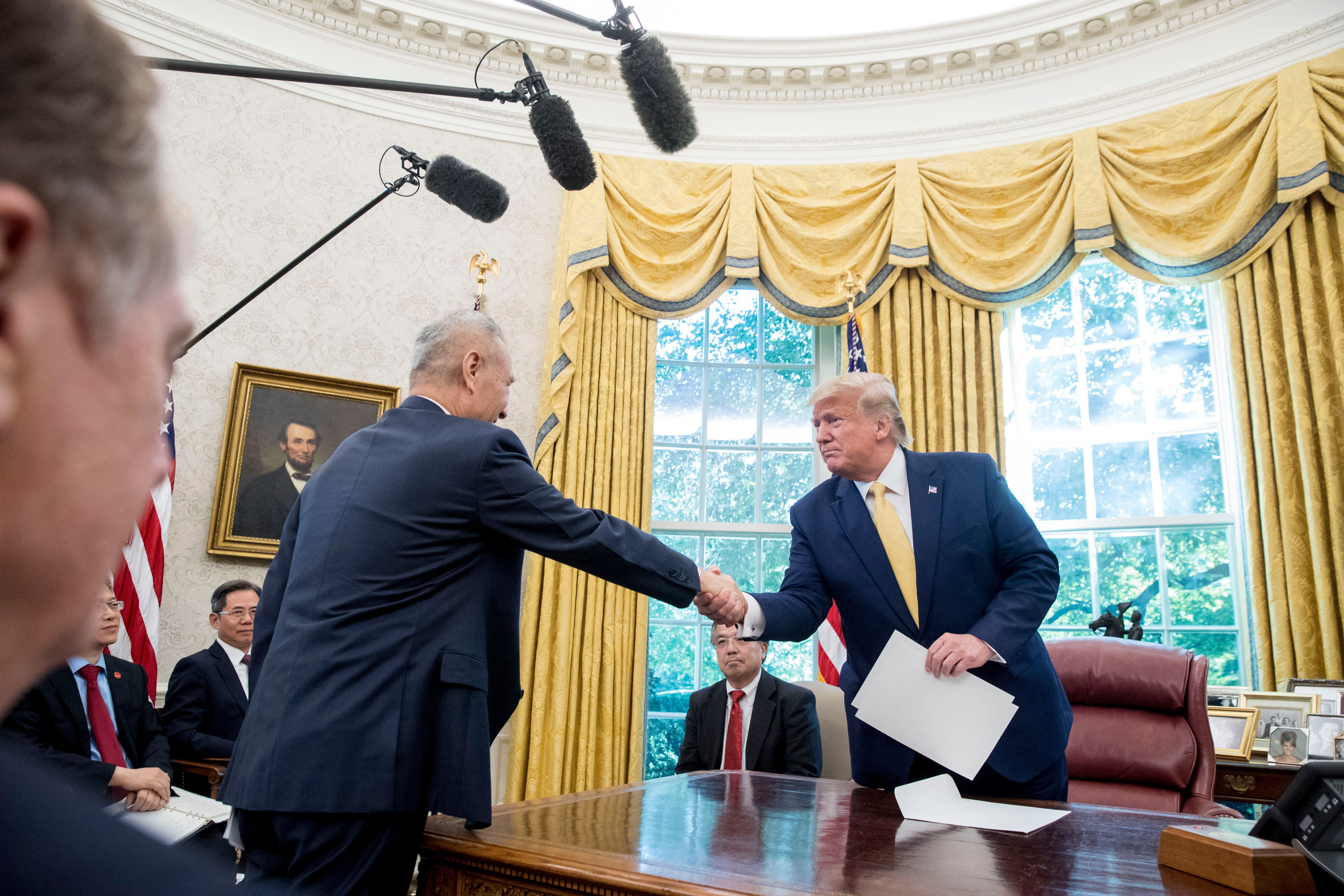 President Donald Trump shakes hands with Chinese Vice Premier Liu He after being given a letter in the Oval Office of the Whi