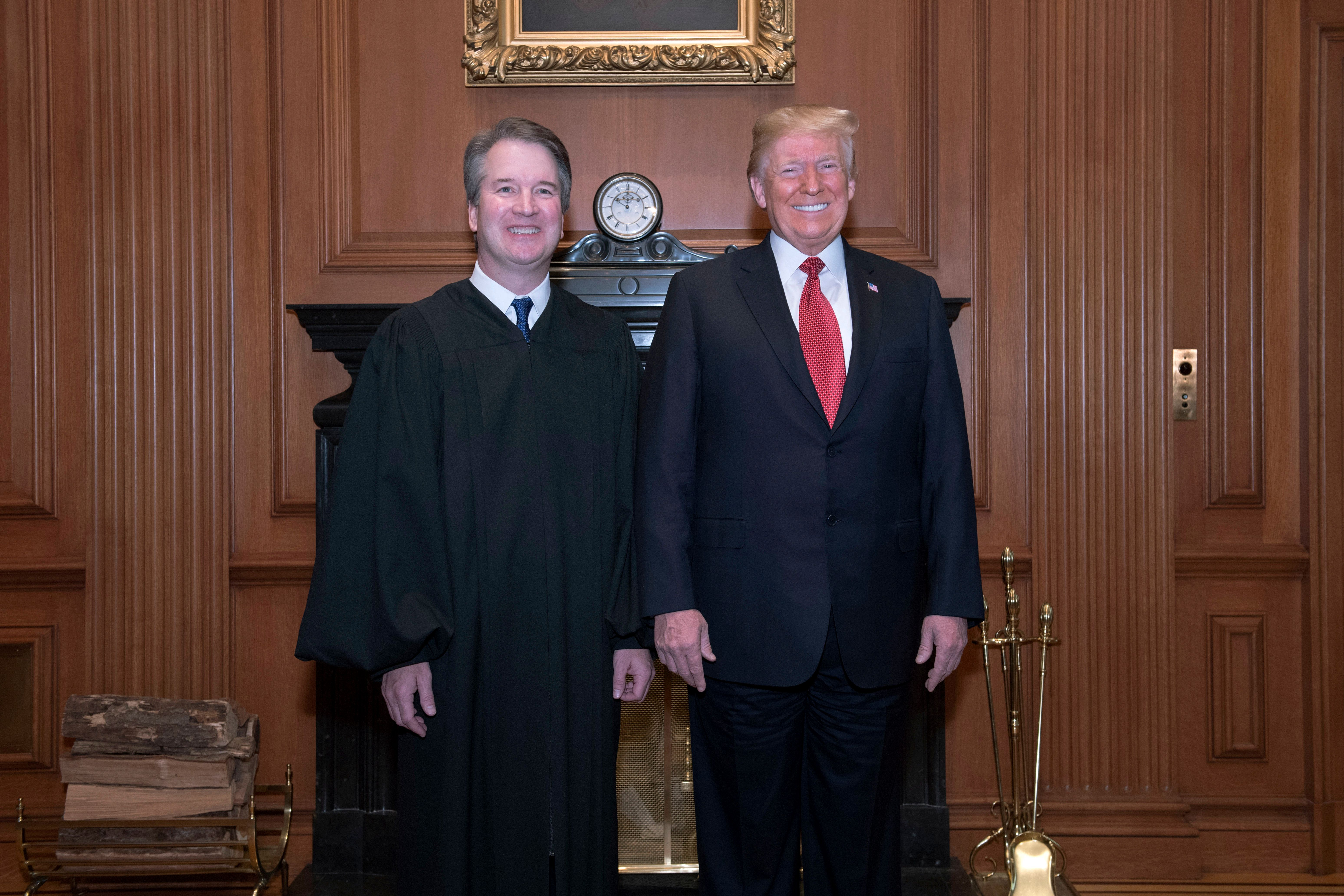 In this image provided by the Supreme Court, President Donald Trump poses with Associate Justice Brett Kavanaugh on Nov. 8, 2
