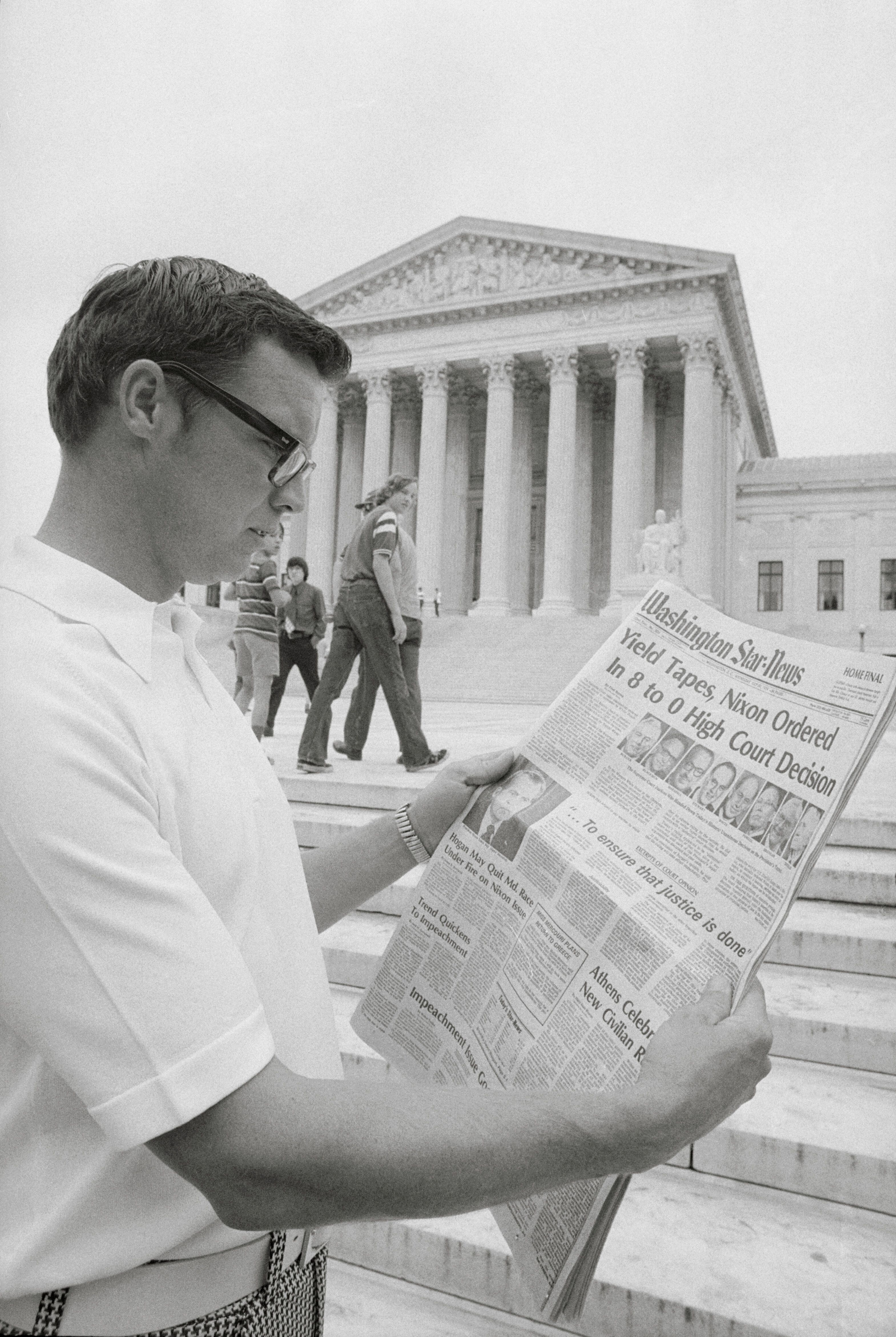 A visitor in the nation's capital reads the headlines in 1974 in front of the Supreme Court telling of the court's ruling ord