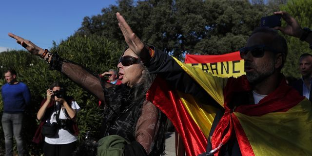 People make the fascist salute as they gather outside Mingorrubio's cemetery, outskirts of Madrid.