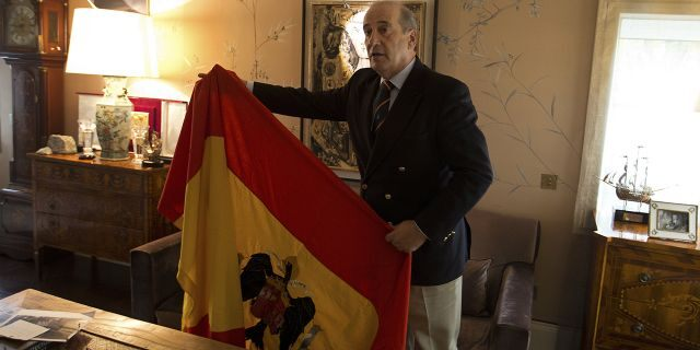Spanish dictator General Francisco Franco's grandson, Francisco Franco Martinez-Bordiu holds up a pre-constitutional Spanish flag he wants draped over the coffin General Franco during his reburial Thursday.
