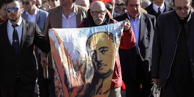 A man holds a drawing of Spanish dictator Gen. Francisco Franco as they gather outside Mingorrubio's cemetery, outskirts of Madrid.