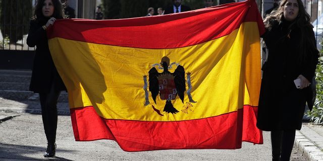 Two women holding a pre-constitutional Spanish flag gather outside Mingorrubio's cemetery, outskirts of Madrid, Thursday, Oct. 24, 2019. (AP Photo/Manu Fernandez)