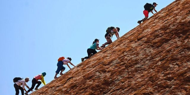 Tourists climb the sandstone monolith called Uluru that dominates Australia's arid center at Uluru-Kata Tjuta National Park, Friday, Oct. 25, 2019, the last day climbing is allowed.