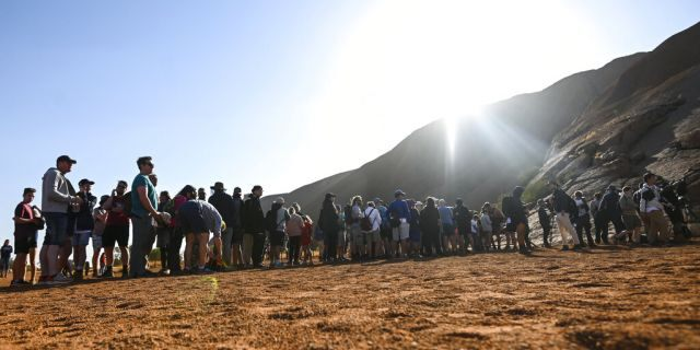 Tourists line up waiting to climb the sandstone monolith called Uluru that dominates Australia's arid center at Uluru-Kata Tjuta National Park, Friday, Oct. 25, 2019, the last day climbing is allowed.