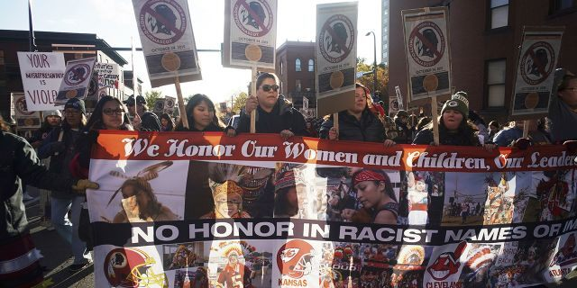 """Protesters march from Peavey Park to US Bank Stadium to protest the use of """"Redskins"""" in the name of the Washington NFL football team, and the names of some other pro sports teams, before Washington's game against the Minnesota Vikings on Thursday, Oct. 24, 2019, in Minneapolis."""