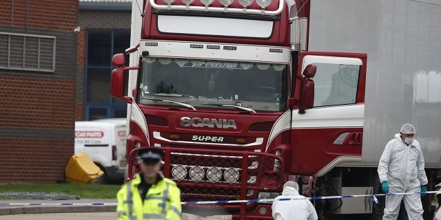 Police forensic officers attend the scene after a truck was found to contain a large number of dead bodies, in Thurrock, South England, Wednesday Oct. 23.