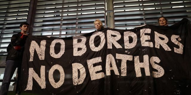 Demonstrators hold a banner during a vigil for the 39 lorry victims, outside the Home Office in London, Thursday, Oct. 24.