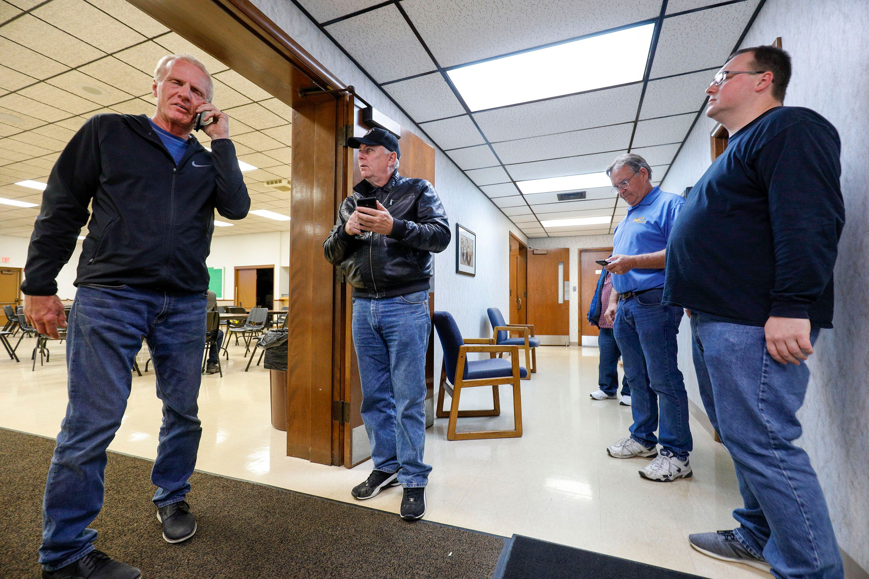 Officials of UAW Local 160 check their phones to get updates on the UAW-GM contract ratification vote count on Oct. 25, 2019