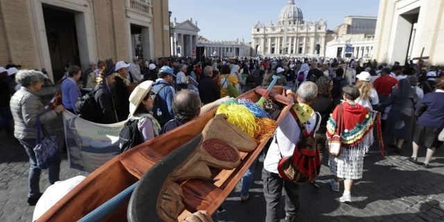 Members of Amazon indigenous populations walk during a Via Crucis, or Way of the Cross, procession to the Vatican. In foreground is a wooden statue portraying a naked pregnant woman. (AP Photo/Andrew Medichini)