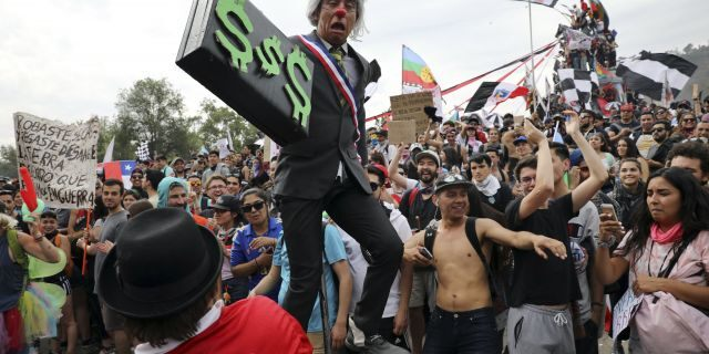 An artist performs as Chile's President Sebastian Pinera holding a briefcase embellished with dollars signs, during an anti-government protest in Santiago, Chile, Friday, Oct. 25, 2019. At least 19 people have died in the turmoil that has swept the South American nation. The unrest began as a protest over a 4-cent increase in subway fares and soon morphed into a larger movement over growing inequality in one of Latin America's wealthiest countries. (AP Photo/Rodrigo Abd)