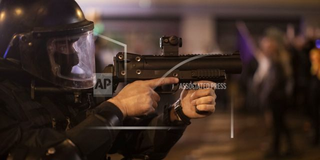 A Catalan police officer aims his weapon against demonstrators during clashes in Barcelona, Spain, Saturday, Oct. 26, 2019. (AP Photo/Emilio Morenatti)