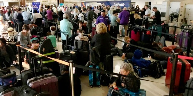Crowds form at Louis Armstrong New Orleans International Airport after the remnants of Tropical Storm Olga knocked power out at the terminal early Saturday. (David Grunfeld/The Times-Picayune/The New Orleans Advocate via AP)