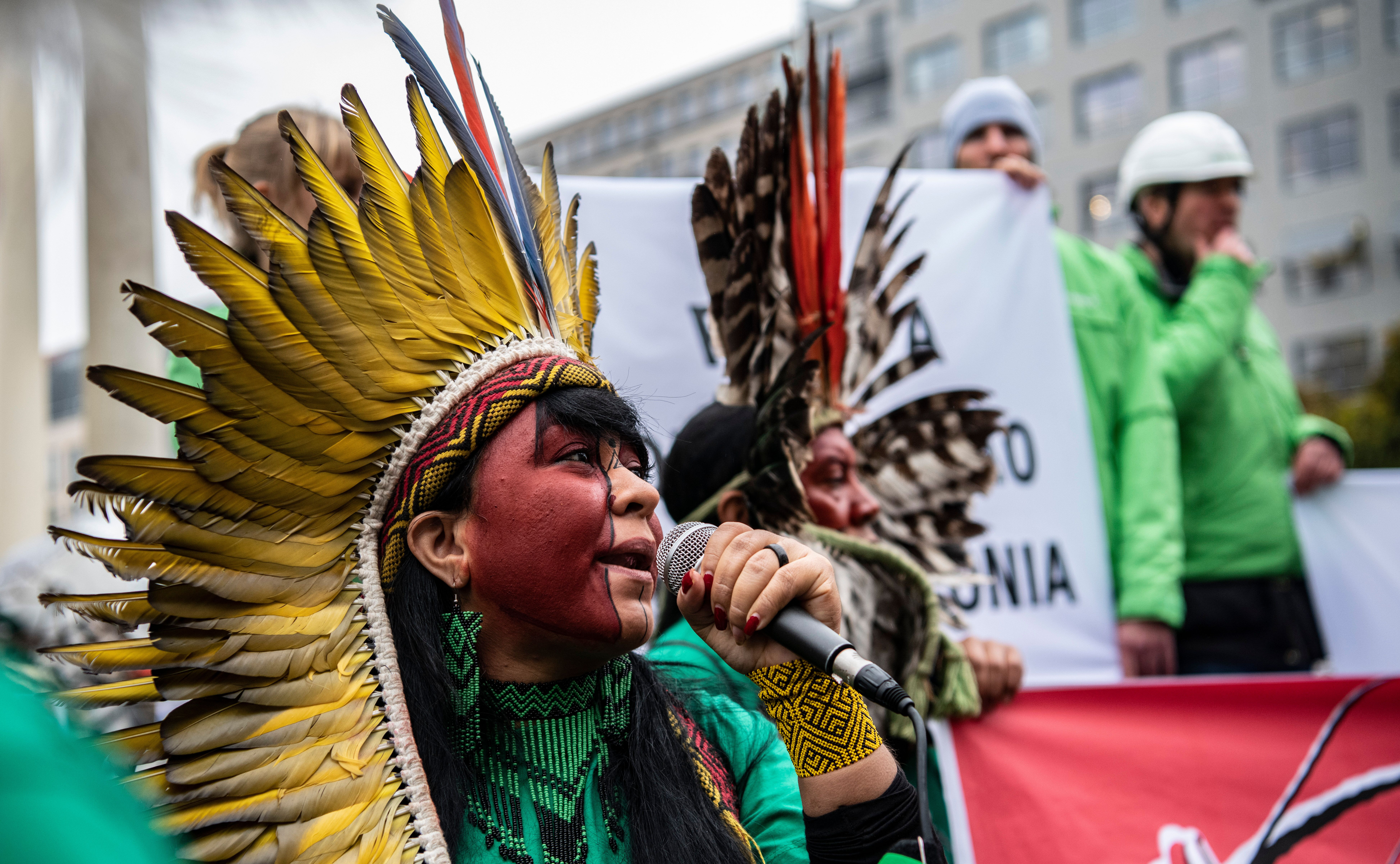 Members of an indigenous delegation from Brazil protest in Berlin to draw attention to the destruction of the Amazon and thre