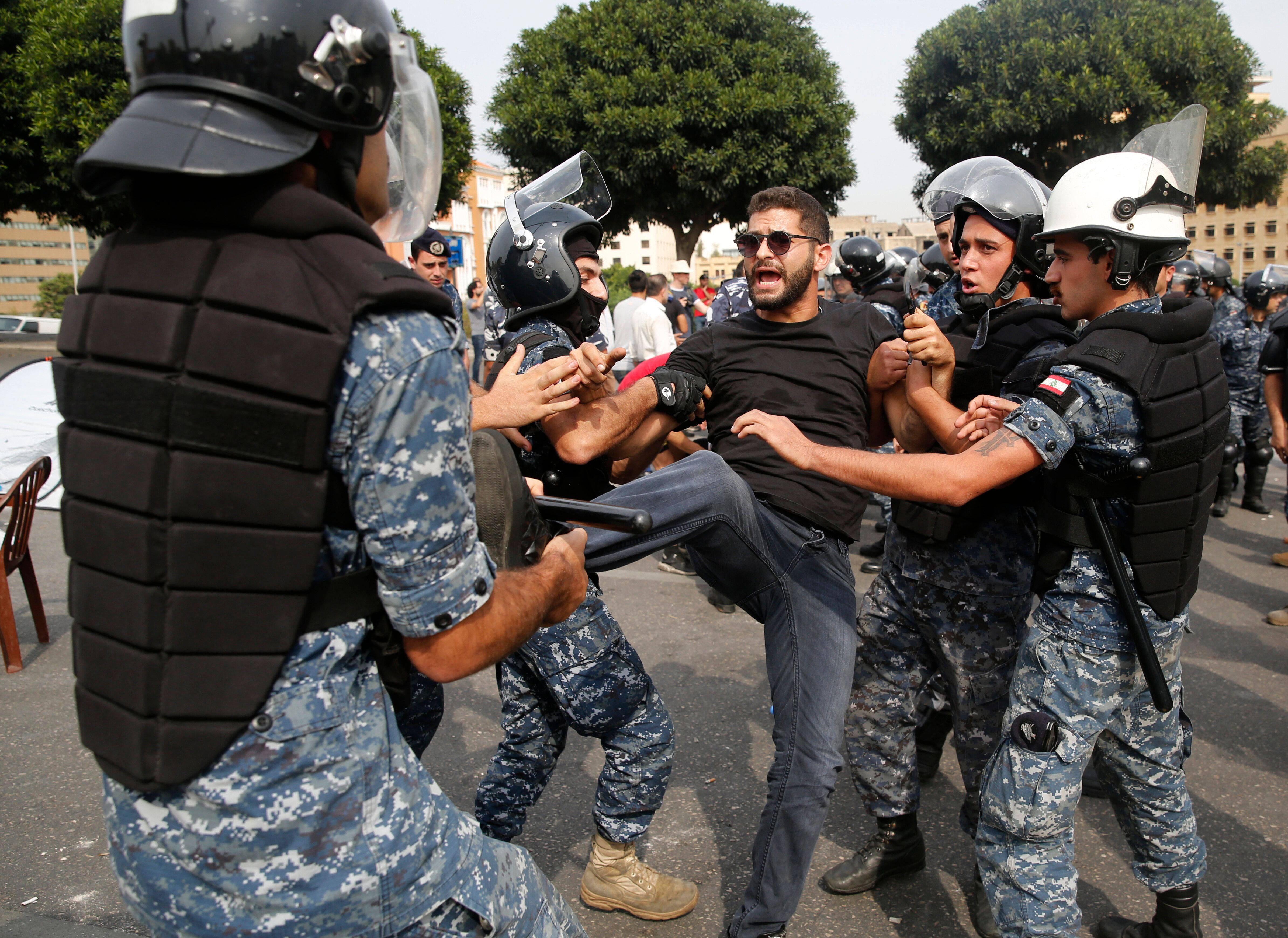 Police remove an anti-government protester blocking a main highway with his body in Beirut, Lebanon, Saturday, Oct. 26, 2019.