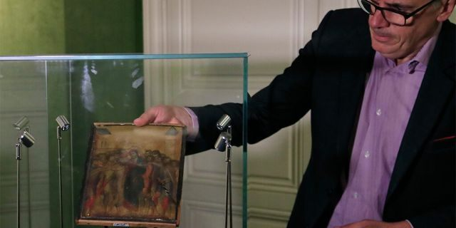 Art expert Stephane Pinta with the painting by Italian master Cimabue in Paris.