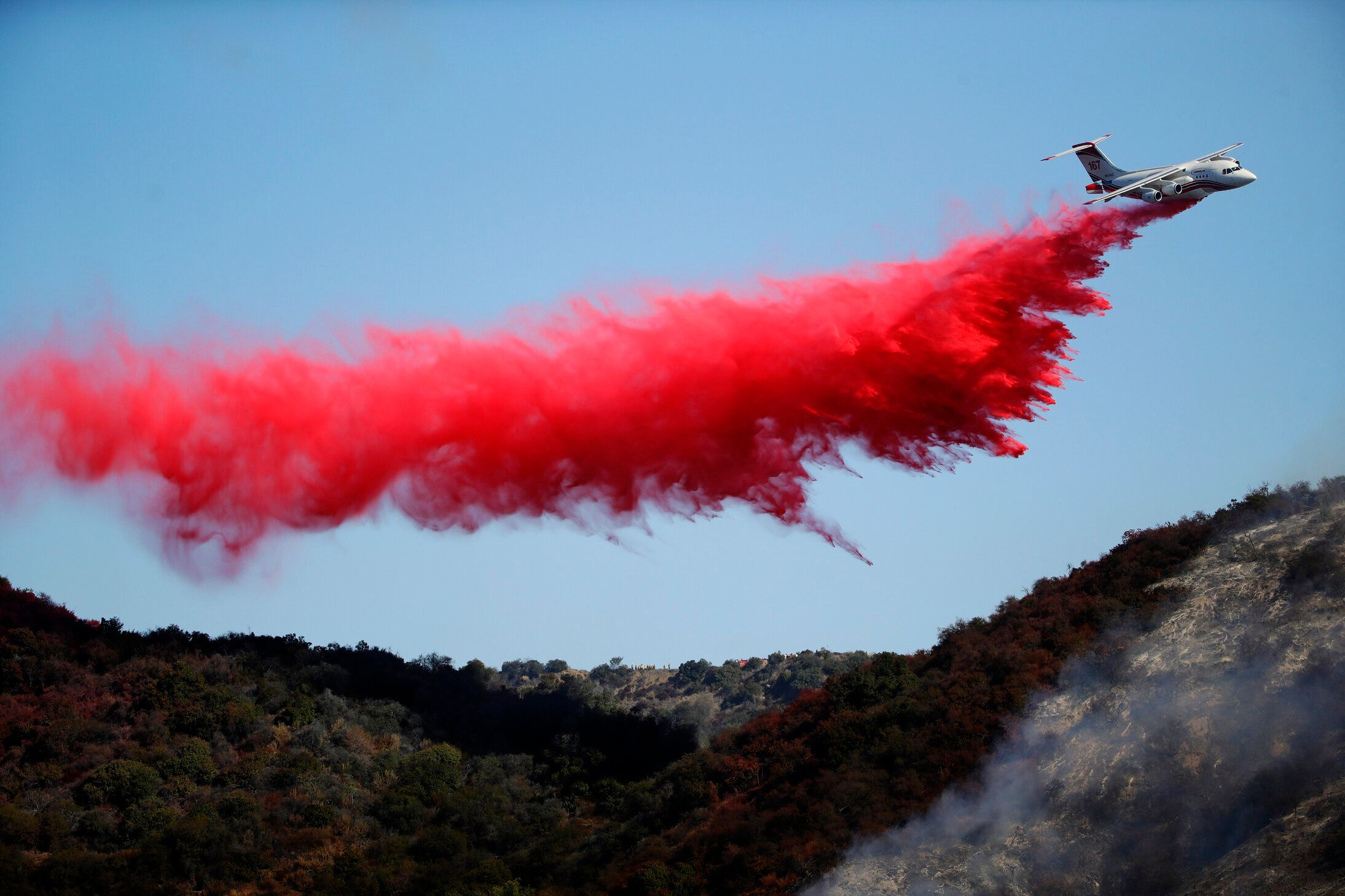 A plane drops fire retardant as the Getty fire burns Monday in Los Angeles' Mandeville Canyon.