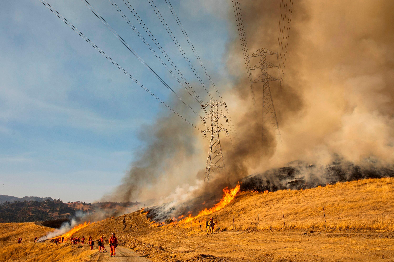 A back fire burns a hillside near PG&E power lines during firefighting operations to battle the Kincade fire in Healdsbur