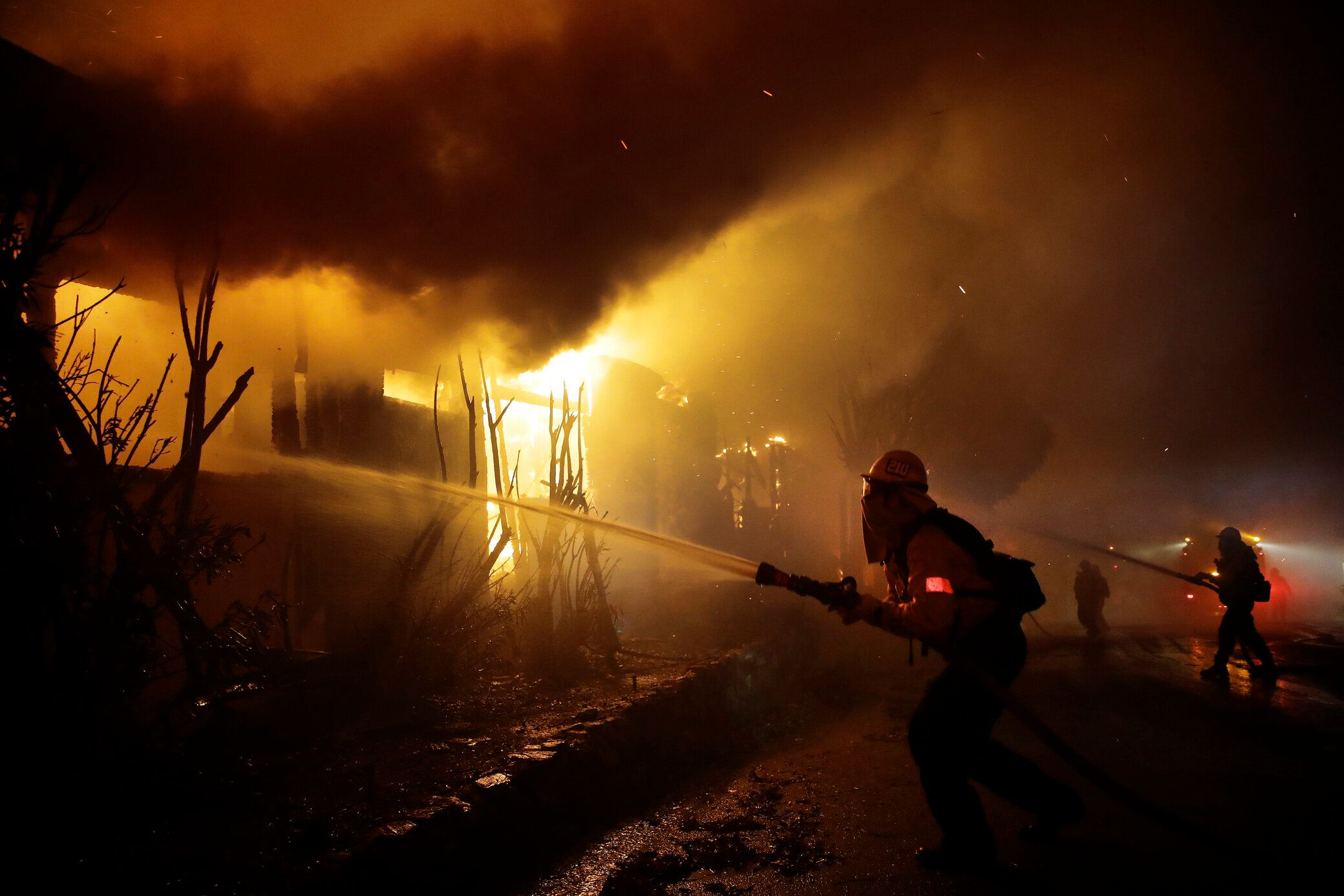 Firefighters try to salvage homes Monday as the Getty fire spreads in West Los Angeles.
