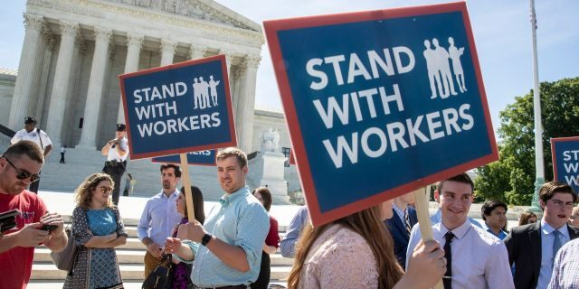 In this Monday, June 25, 2018, file photo, people gather at the Supreme Court awaiting a decision in an Illinois union dues case, Janus vs. AFSCME, in Washington.
