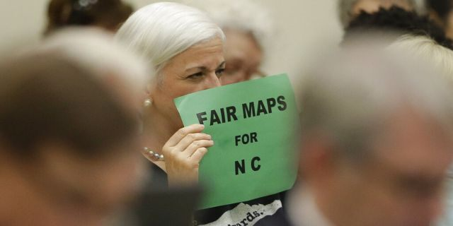 In this July 26, 2017 photo, a member of the gallery tried to display her sign while lawmakers conveneD during a joint select committee meeting on redistricting in Raleigh, N.C. North Carolina judges on Monday blocked the state's congressional map from being used in the 2020 elections. (AP Photo/Gerry Broome, File)