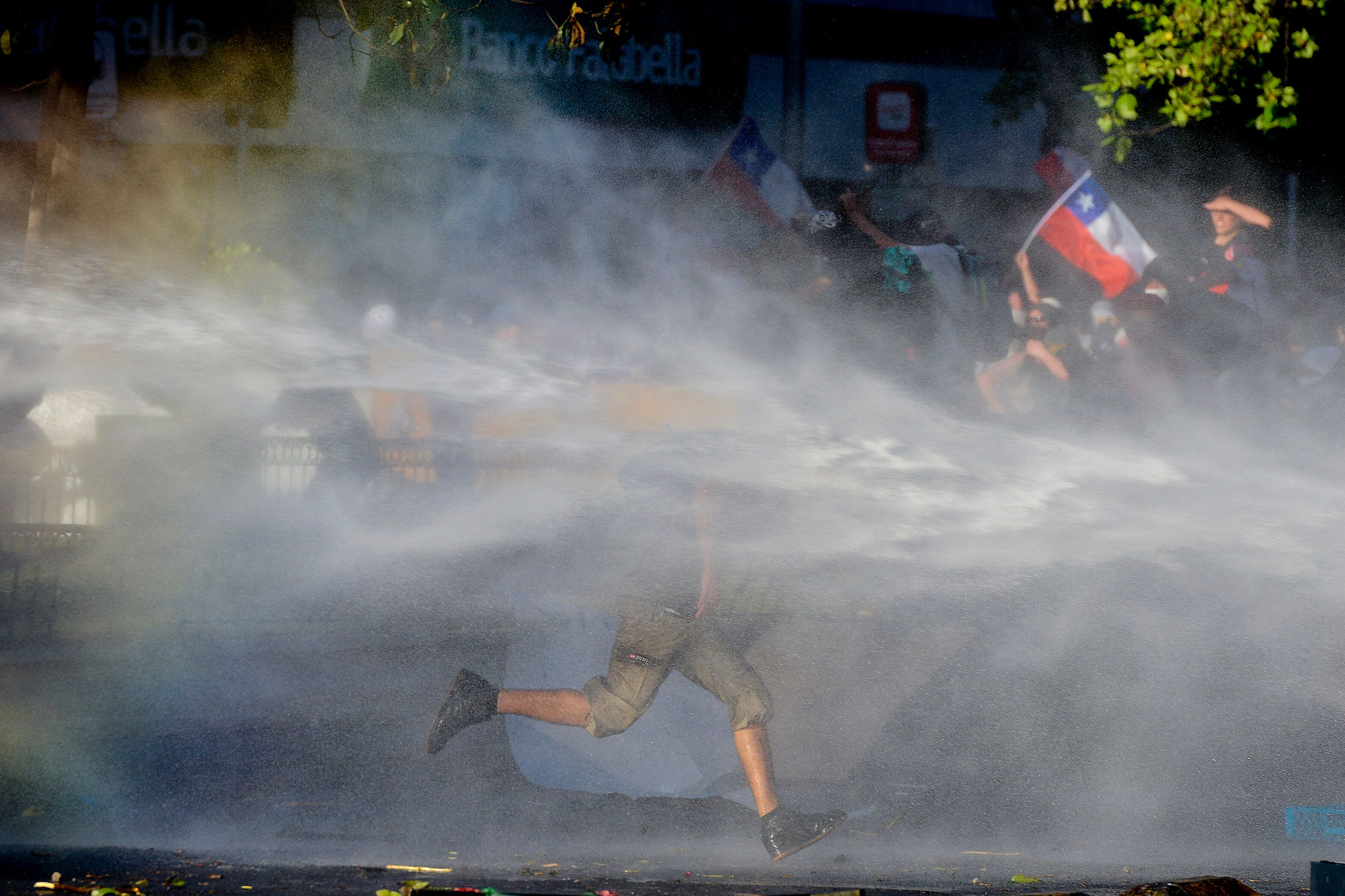 An anti-government protester runs through spray coming from a police water cannon in Santiago, Chile, on Oct. 28, 2019.