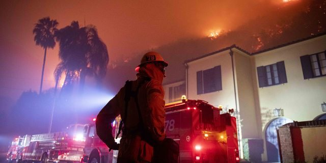 A firefighter watches a flames approach the Mandeville Canyon neighborhood during the Getty fire, Monday, Oct. 28, 2019, in Los Angeles, Calif.