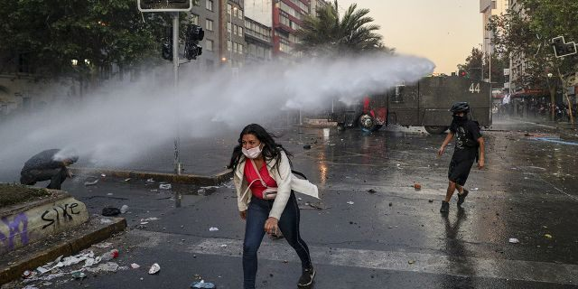 An anti-government protester walks away from the spray of a police water cannon in Santiago, Chile, Tuesday, Oct. 29, 2019.