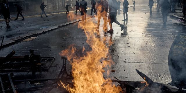 Anti-government protesters walk past a burning barricade set fire by protesters during clashes with police in Santiago, Chile, Tuesday, Oct. 29, 2019. (AP Photo/Rodrigo Abd)