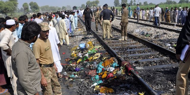 Pakistani soldiers and officials examine a train damaged by a fire in Liaquatpur, Pakistan, Thursday, Oct. 31, 2019. A massive fire engulfed three carriages of the train traveling in the country's eastern Punjab province