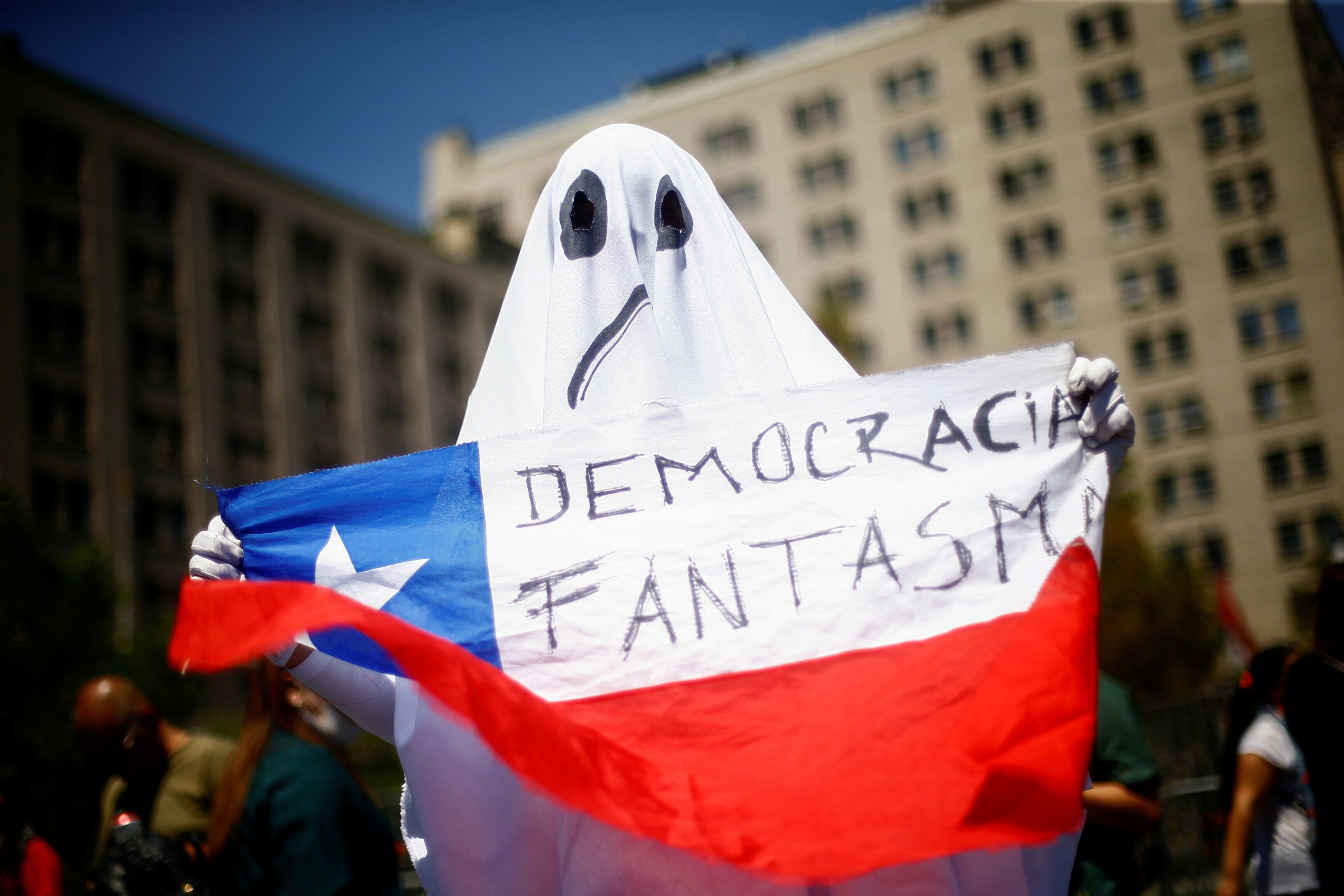 """A demonstrator dressed as a ghost holds a Chilean flag with the legend """"ghost democracy"""" during anti-government protests in S"""